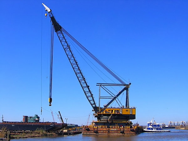 Moving Barge 1: A huge waterborne crane is moving a new barge from land to water