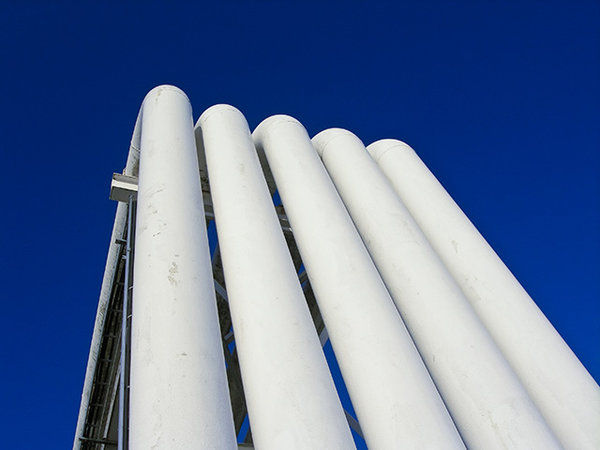 Industrial: Some white industrial pipes against a blue sky