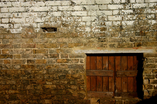 Peek A Boo: An old wooden hatch in a very odd placed, positioned in the centre of a grimy stone brick wall.