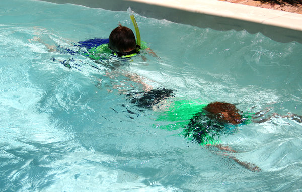 in the pool: young boys swimming and snorkeling in the swimming pool
