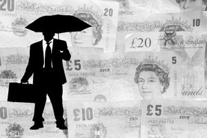 Business Rain: Business man holding an umbrella against a background of sterling bank notes