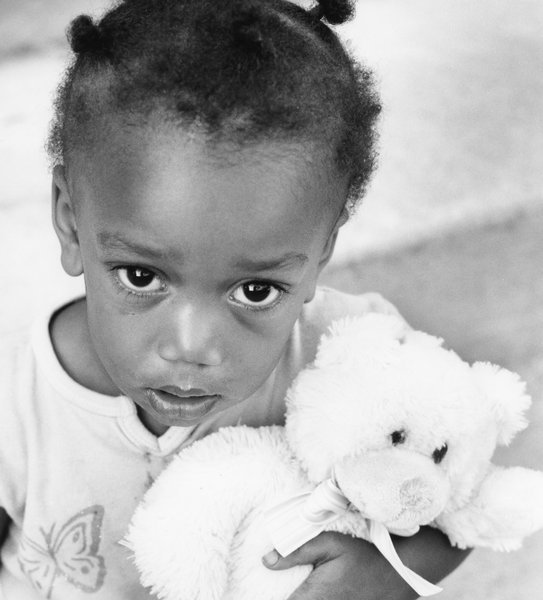 Child with Teddy Bear: Young child clutching on to cherished posession