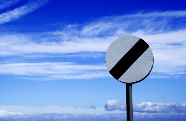 No Limits: Speed limits sign against cloudy blue sky.