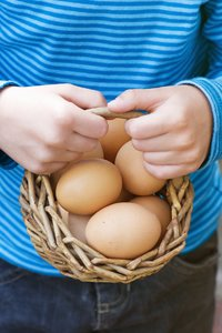 Fresh eggs: little child holding fresh eggs in a basket just before three eggs dropped to the floor ;-)