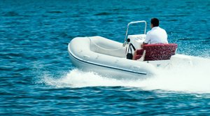 Summertime Leisure: A man driving speedboat in summertime