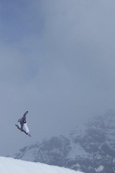 OVER THE TOP: snowboard rider flying over the top of the mountain
