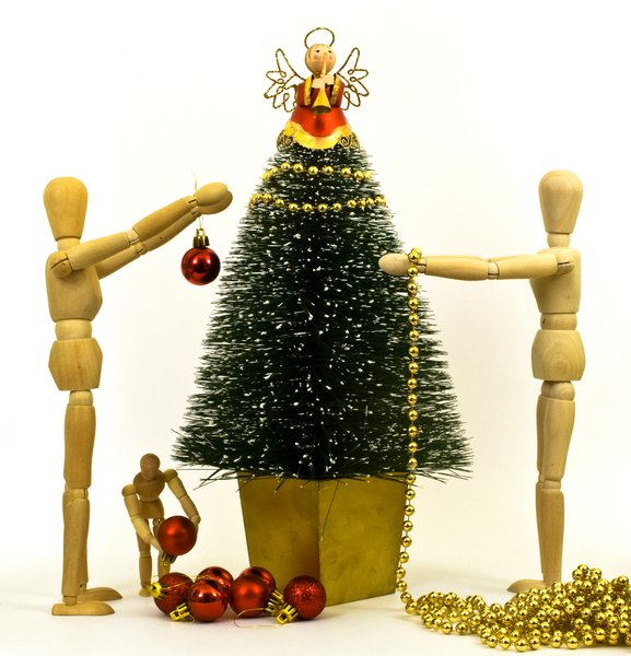 Dressing the Tree: Wooden mannequin family decorating a minature Chrismas tree.