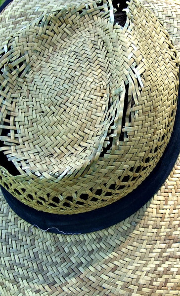 frayed hat: frayed crown of old straw hat