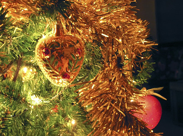 Antique Ornament and Garland: An antique ornament and garland on a Christmas tree with a golden glow.