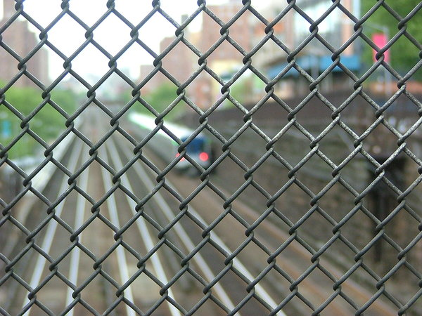 New York Subway Through Fence: Looking down through metal fence as subway train goes by in Upper East Side NYC