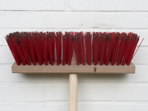 Broom: Broom with red bristles leaning against a white wall