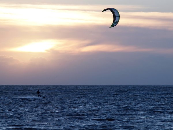 Kite surfer in backlight: Kitesurfer in the last sunlight.