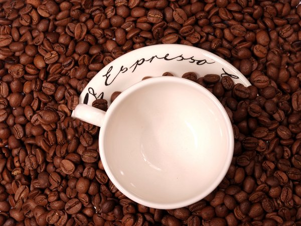 Coffee beans and an espresso c: An espresso cup and saucer in coffee beans