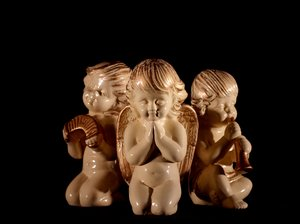 Angels band: Three angels. Two playing an instrument and one praying. Black background.