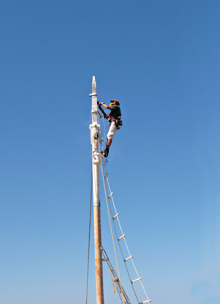 up the mast: workman - rigger doing renovating and maintenance work on pearling lugger's mast