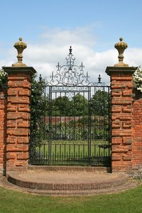 Garden gate: An old ornate gate to a garden in the grounds of a manor house in Warwickshire, England.