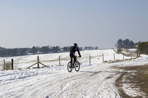 Cyclist in the snow: A cross-country cyclist on the South Downs, West Sussex, England, in February snow.