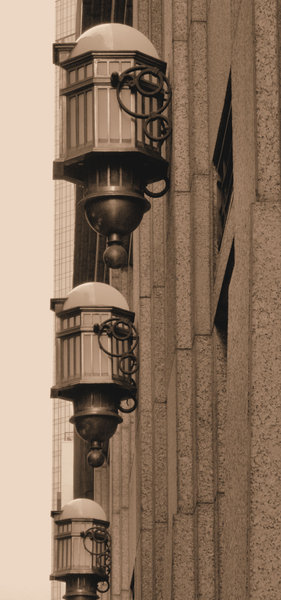 sepia light wall: distinctive external light fittings on historic city building wall
