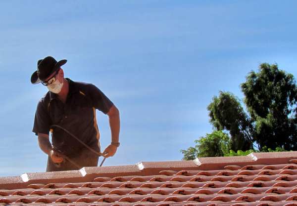 roof restoration14: workman cleaning and painting roof tiles for restoration
