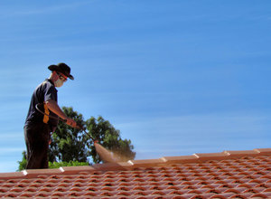 roof restoration13: workman cleaning and painting roof tiles for restoration