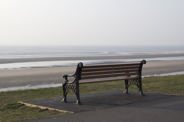 Bench by the sea at dawn: A Victorian bench by the sea at Blackpool, England, at dawn.