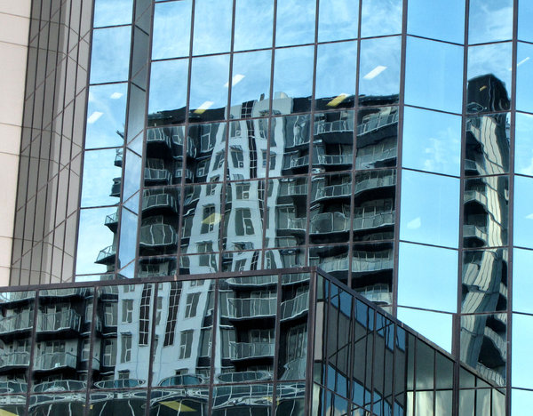 highrise reflections11: glass, concrete and steel commercial building in  reflecting nearby buildings and sky in its windows