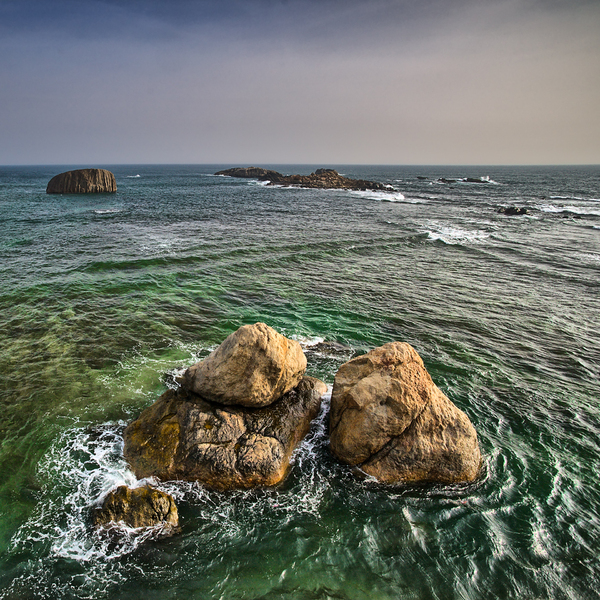 Rocks in the Ocean: Huge Rocks of yellowish Granite in turquoise- and green Water. Seen at the Coastline of Galle, Sri Lanka.