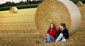 Two Girls sitting in Field wit: Two Girls sitting in a Field, leaning on a huge round Straw Bale
