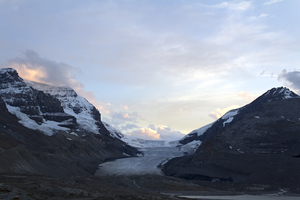 Glacier at dawn: A glacier at dawn in the Rocky Mountains, Canada. The glacier is currently in retreat; formerly it covered the area in the foreground, hence the scraped rocks and mounds of debris.
