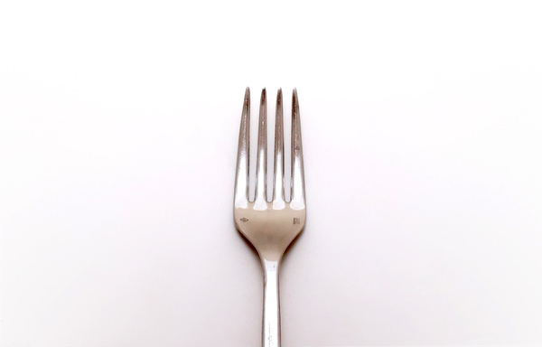 Fork: Vertical view of a fork over a white background.