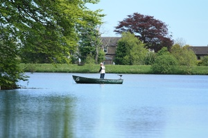 Man on a boat, fishing: Man on a boat on a reservoir, fishing
