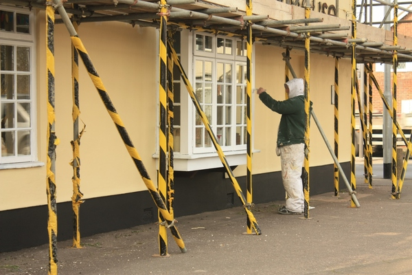Painter: A painter working on the exterior of a pub