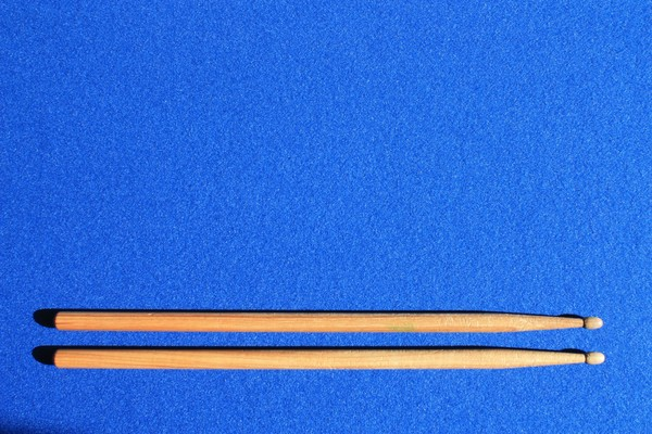 Drumsticks: Wooden drumsticks on a blue pinboard background