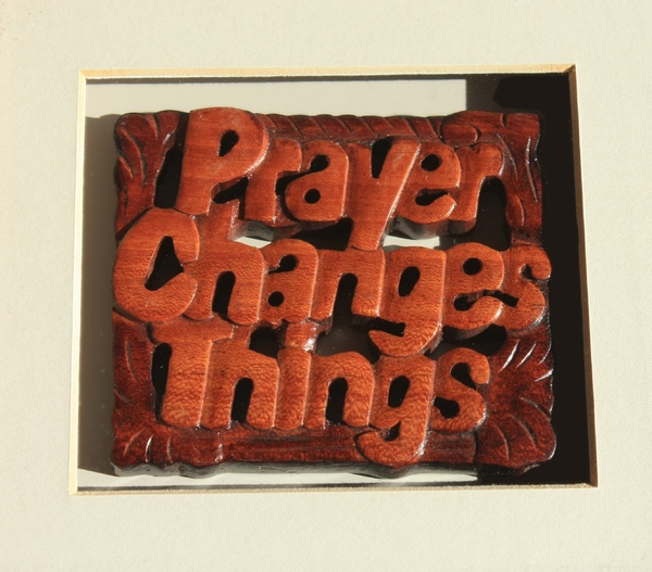 Prayer Changes Things: Close-ups of carved wall hanging