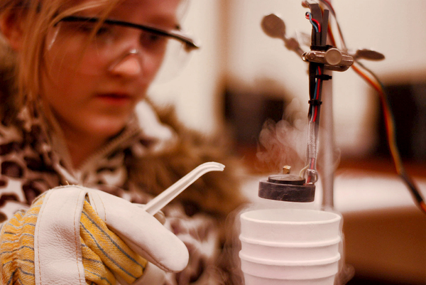 Science Girl: Young girl performing a scientific experiment with gloves and safety glasses.