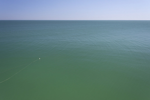 Placid aquamarine sea: A fishing buoy and nets in an unusually placid blue-green sea off southern Italy.