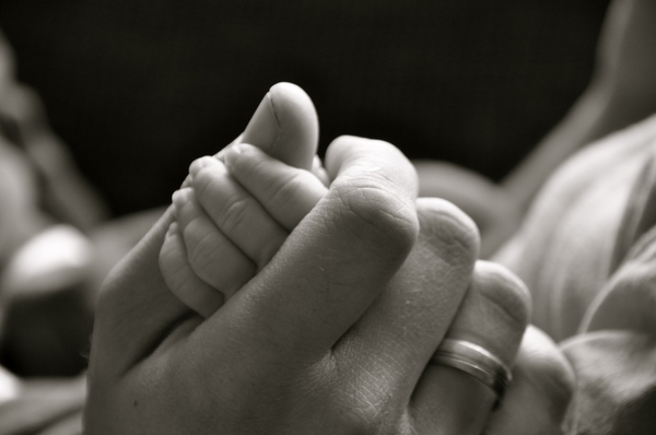 Hands: A father hand holding the small hand of his son