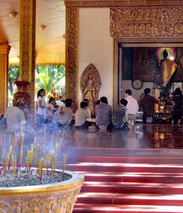 temple devotion1: worshipers and incense at Cambodian Buddhist temple