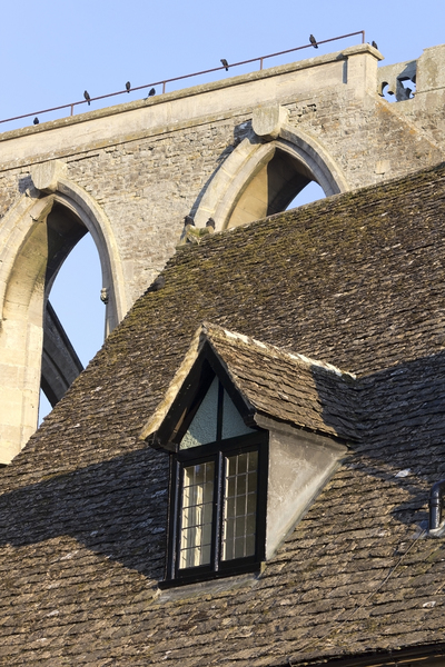 Elements of old architecture: A dormer window of an ancient house with the remains of an abbey in the background in evening sunlight in Wiltshire, England.
