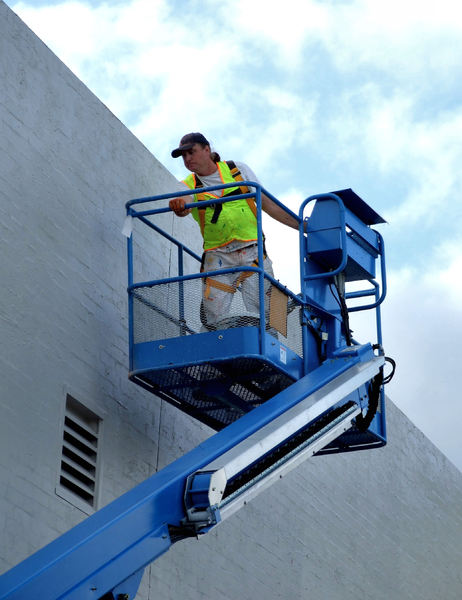 painting on high3: workman painting wall in raised cherry picker