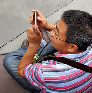 happy snapper2bc: seated roadside onlooker snapping pic on his mobile phone