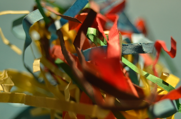Crumpled colored paper shreds : Close-up of a crumpled ball of colored paper strips/shreds.