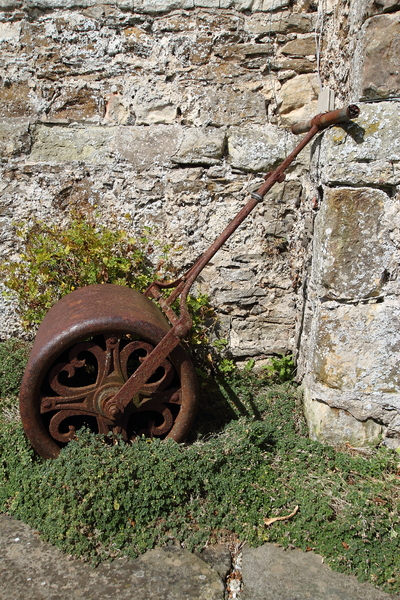 Garden roller: A rusty garden roller amongst green plants against a rustic stone wall