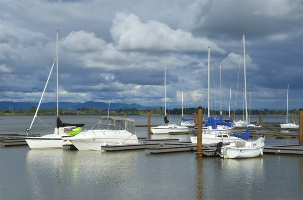 Boats at dock over cloudy sky