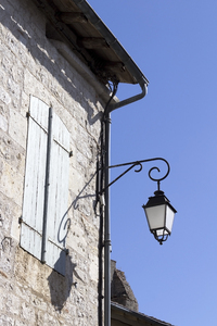 Streetlamp: A streetlamp on an old house in the Lot region of France.