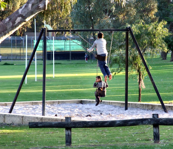 in the swing of things3: boys playing on suburban playground swings
