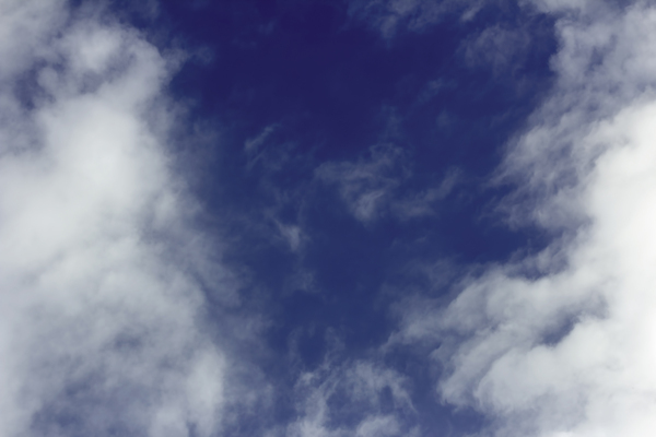 Break in the Clouds: A blue patch of sky with bright clouds on both sides