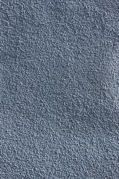 Wall texture: Plastered wall with applied surface texture painted blue, photographed in oblique light.