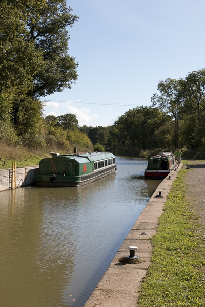 Boats on a canal: A barge and a narrowboat on a canal in West Sussex, England.