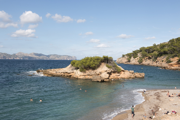 Tiny island with swimmers: A tiny island popular with swimmers on the coast near Alcúdia, Majorca, Balearic Islands, Spain.